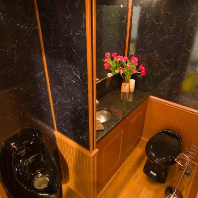 wedding-restroom-rentals-black-toilet-oak-flooring.jpg